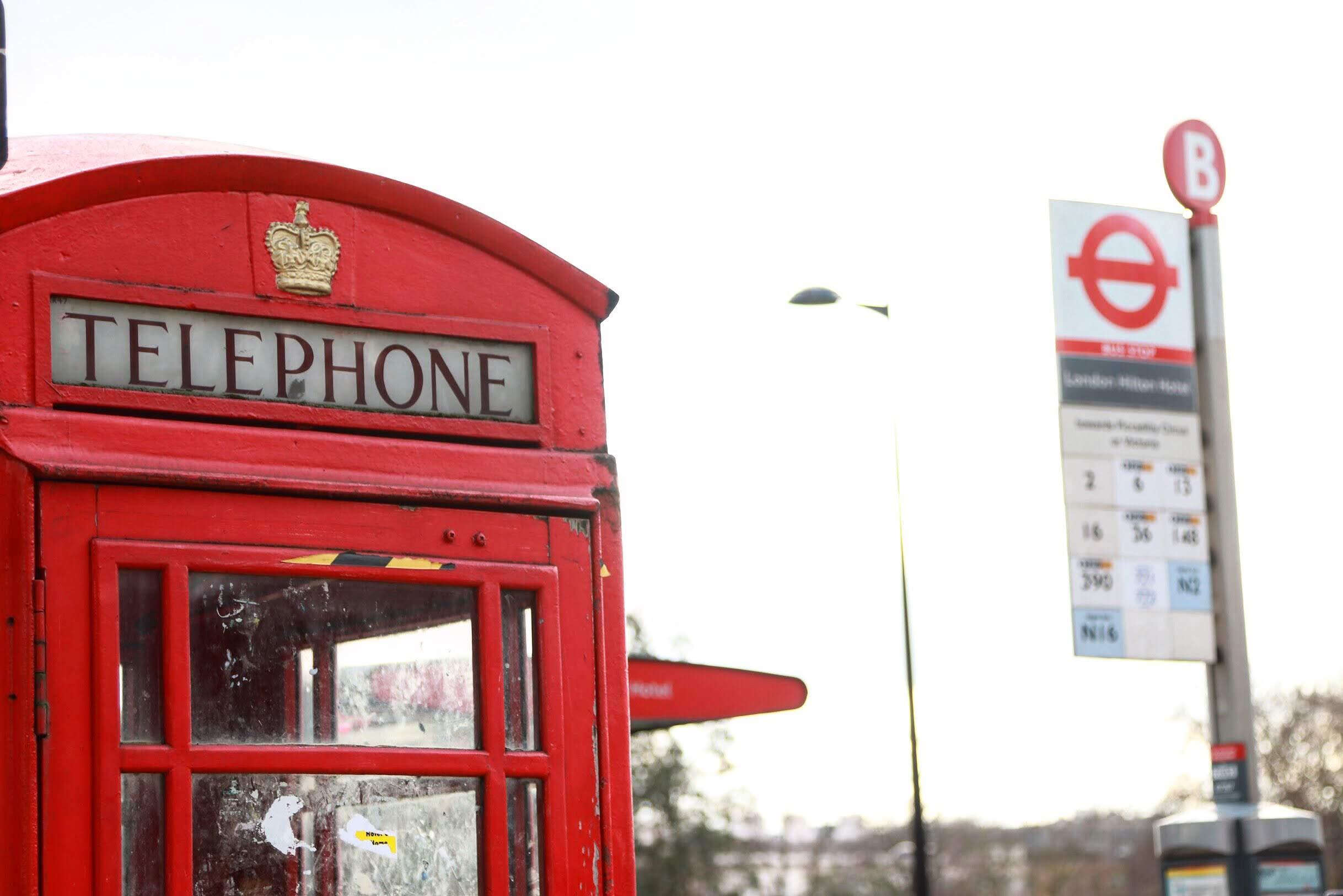 cabine telefônica vermelha de Londres com parada de ônibus desfocada ao lado
