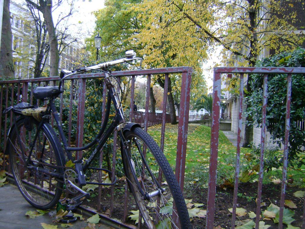bicicleta antiga amarrada num portão de ferro em um parque
