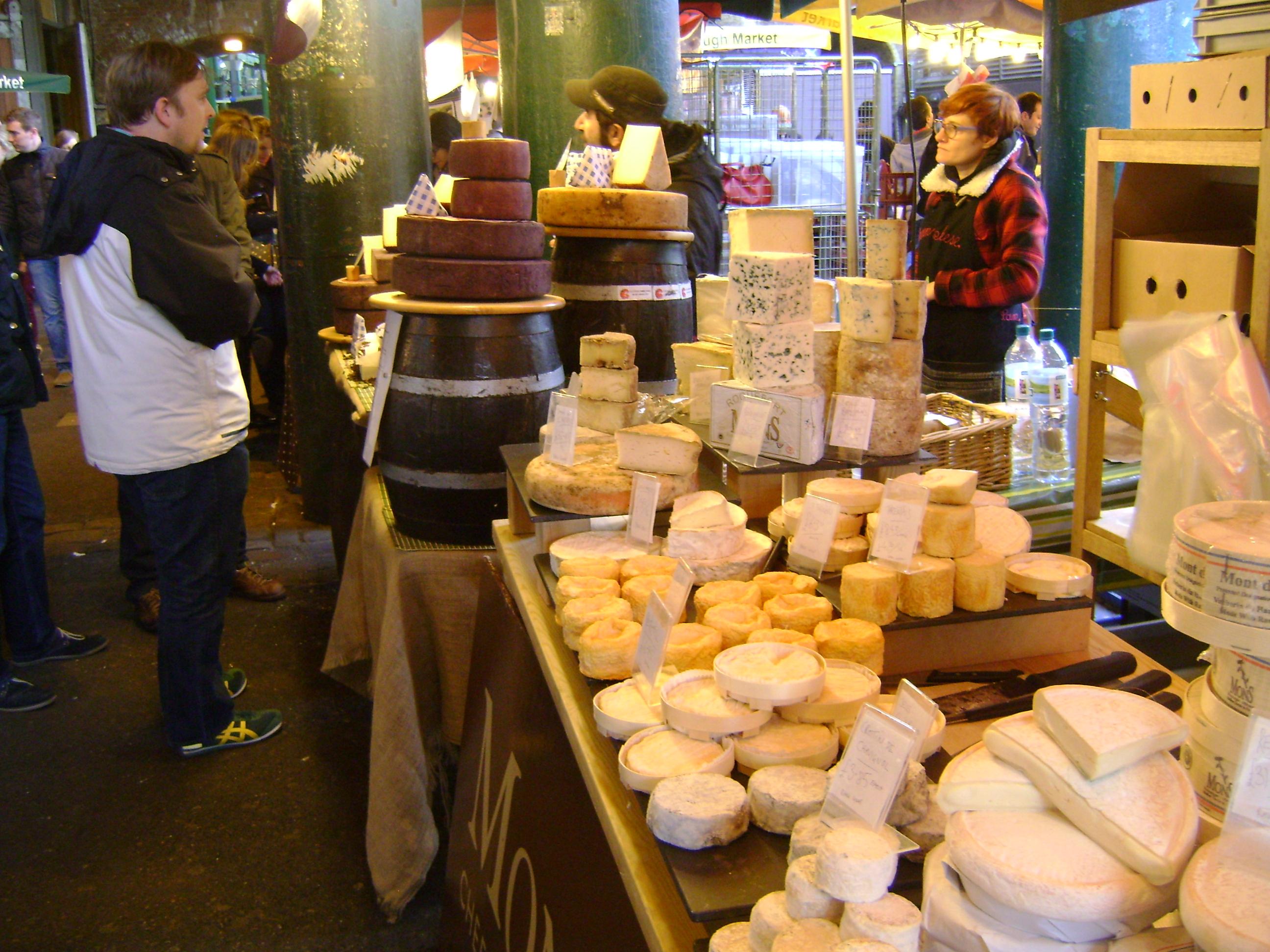 pessoa comprando e vendendo queijos no borough market, mercado publico de londres