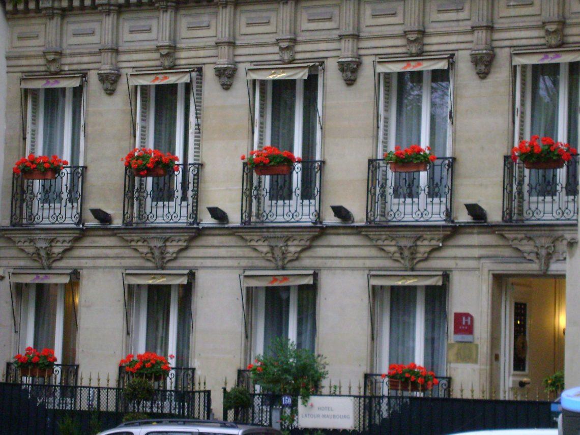 Prédio clássico com flores vermelhas na fachada em Paris