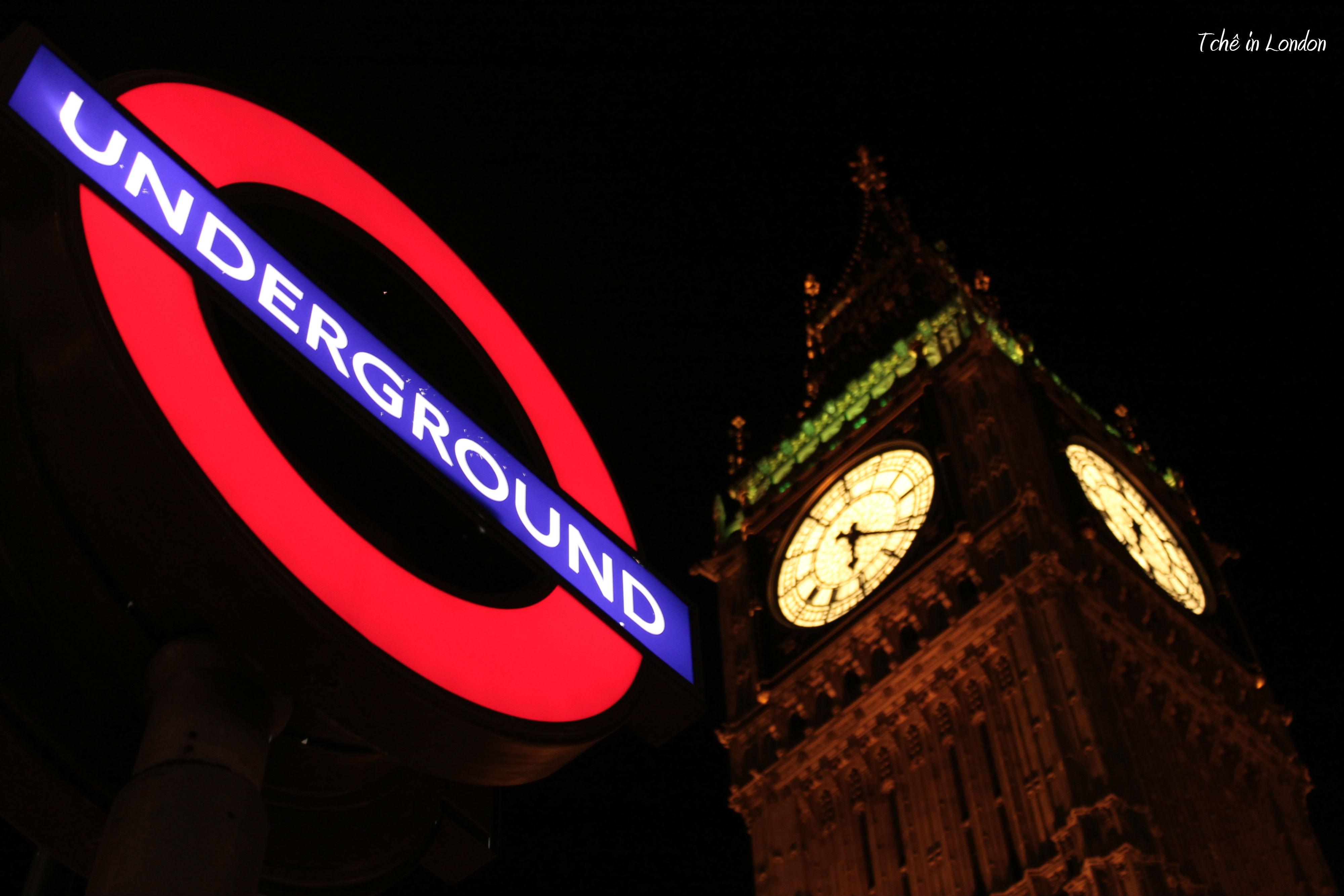 símbolo do metrô de londres com o big ben ao fundo iluminado, à noite
