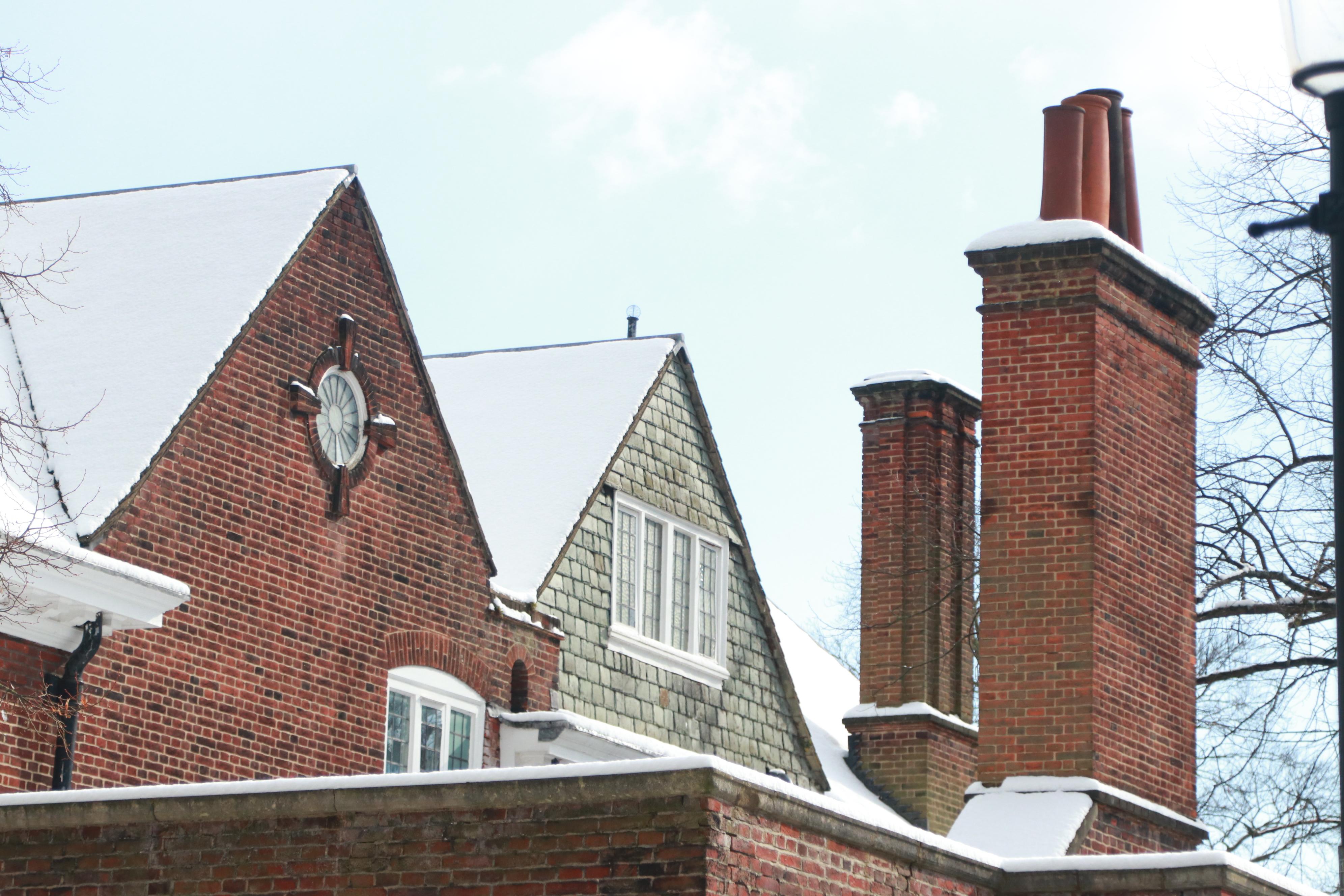 telhado de casas britânicas com neve. Tijolos à mostra.