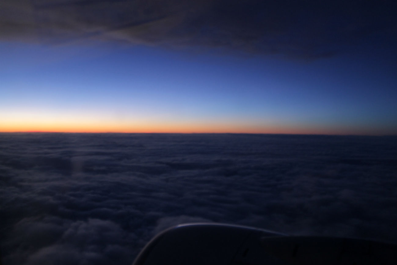 nascer do sol da janela de um avião com nuvens