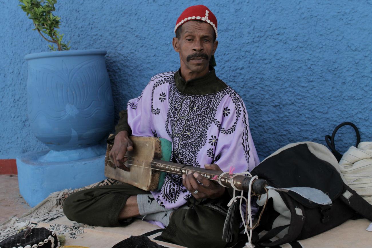 tocador de banjo instrumento musical de cordas no marrocos usando um chapeu vermelho e roupa rosa
