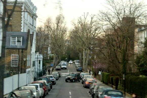 rua de londres com um taxi preto fazendo uma curva no meio da rua. Tradicional, salário mínimo viver em Londres.