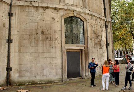 Igreja St. Clement Danes (capela da RAF) com marcas de bombas da segunda guerra mundial. Guia explicando e várias pessoas prestando atenção.