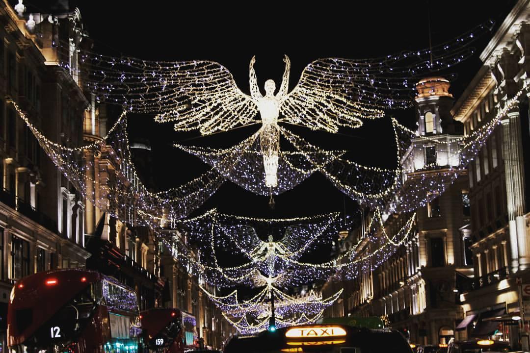 Regent street londres com luzes de Natal. Anjos iluminados voando por cima da rua à noite. Natal.