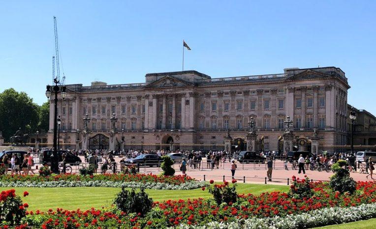 palacio de buckingham com muit agente na frente e bandeira estandarte real com a rainha elizabeth ii em residência e jardins floridos em londres