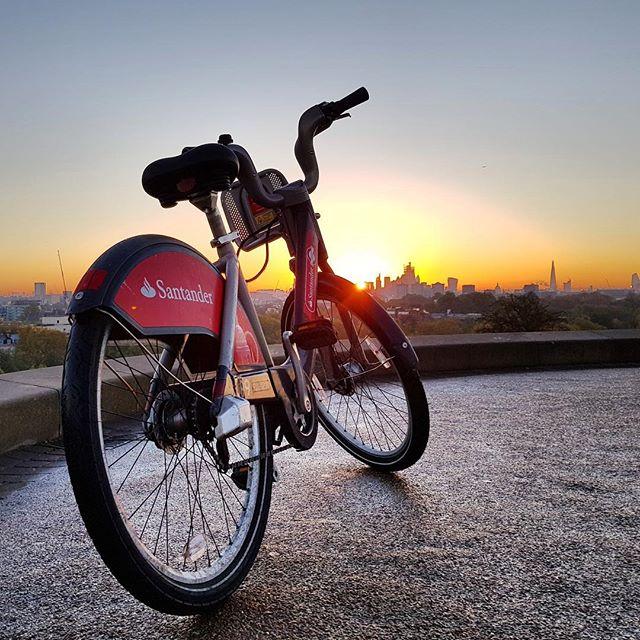 bicicleta do santandes da prefeitura de londres estacionada em primrose hill com predios e por do sol ao fundo