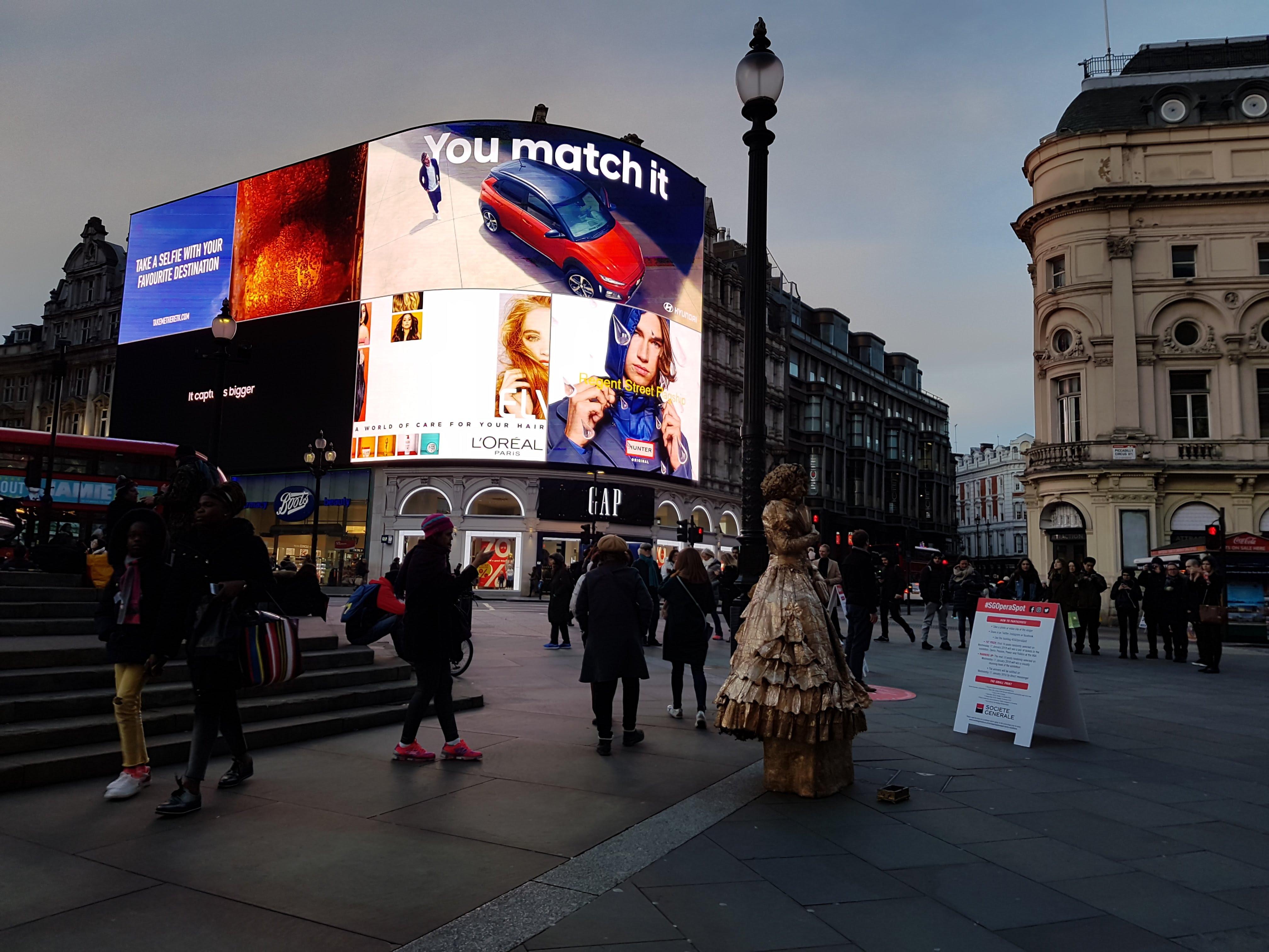 Piccadilly Circus, Londres, à noite. Um artista de rua fazendo de conta que é um estátua humano com muita gente ao redor num fim de tarde. Anúncio da Coca-Cola e de carro no novo telão 4k