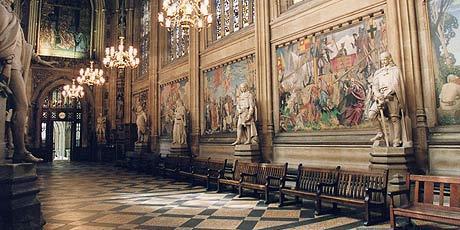 St. Stephen's Hall no Palácio de Westminster com pinturas na parede e esculturas. Lustres bonitos e chão preto e branco.