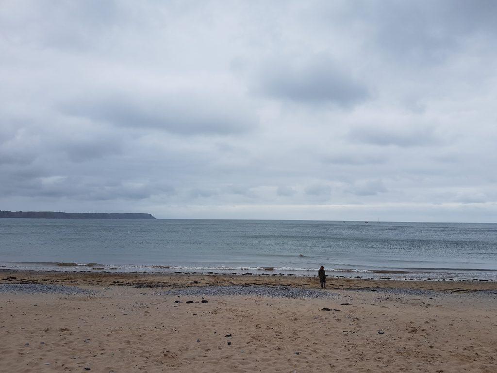 Costa do país de gales. Mar do Reino Unido com pessoa caminhando num dia frio e tempo nublado.