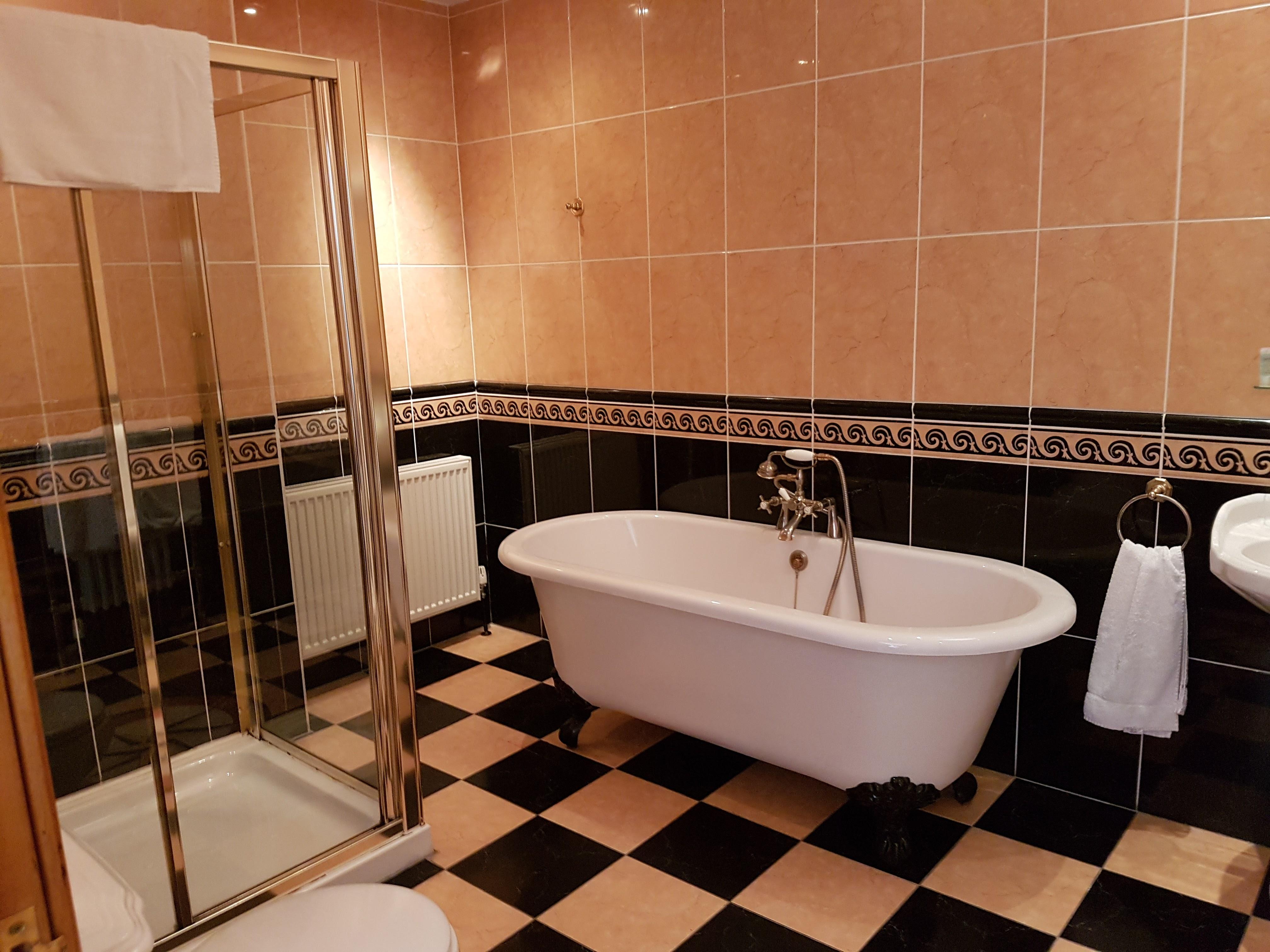 banheira com detalhes em dourado em um banheiro de um castelo no país de gales. Taolhas penduradas, chão xadrez e paredes de azulejo vitorianas.