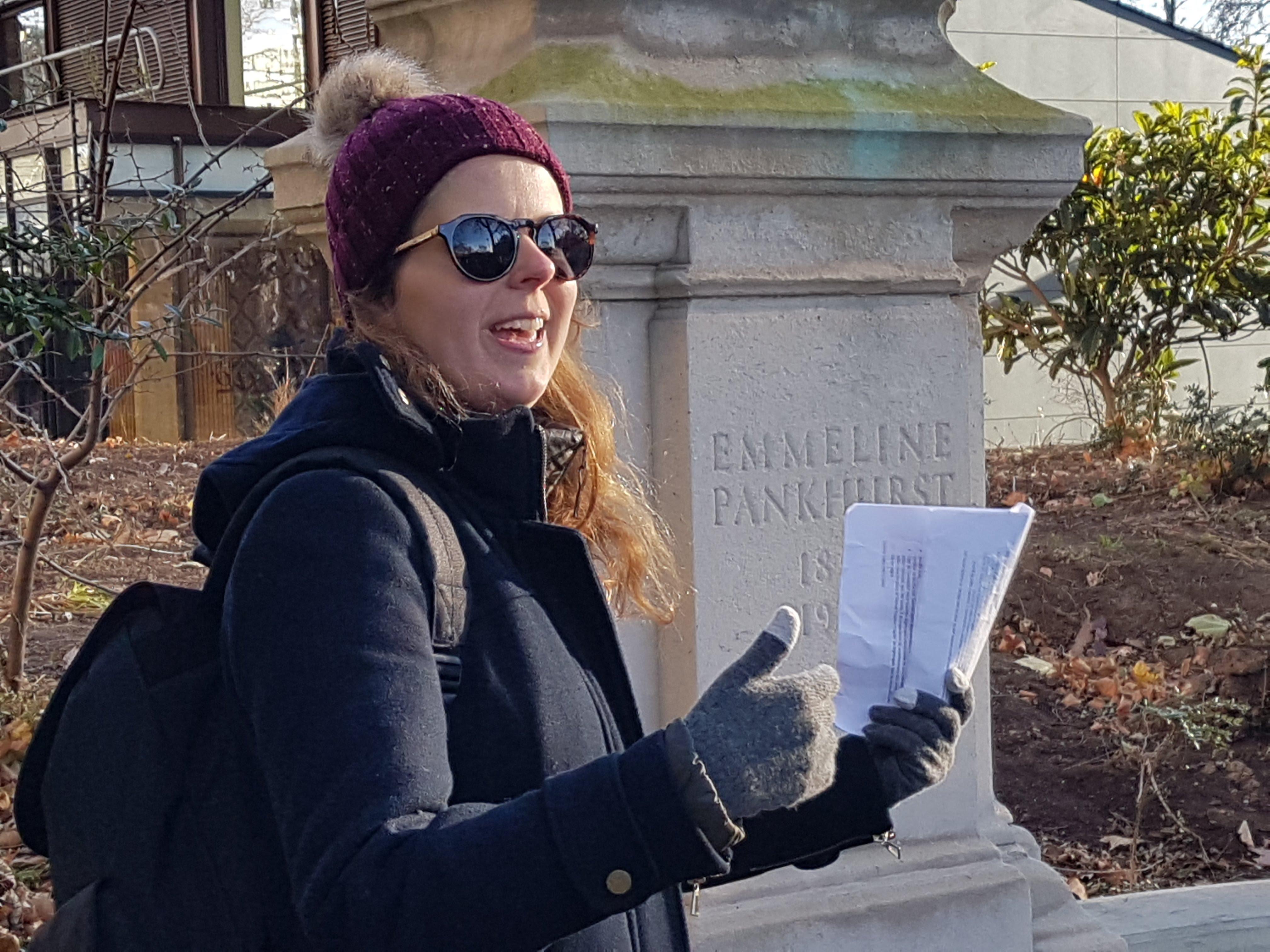 Helô Righetto mulher falando sobre emeline pankhurst uma das suffragettes ao lado de uma estátua ao lado do parlamento britânico