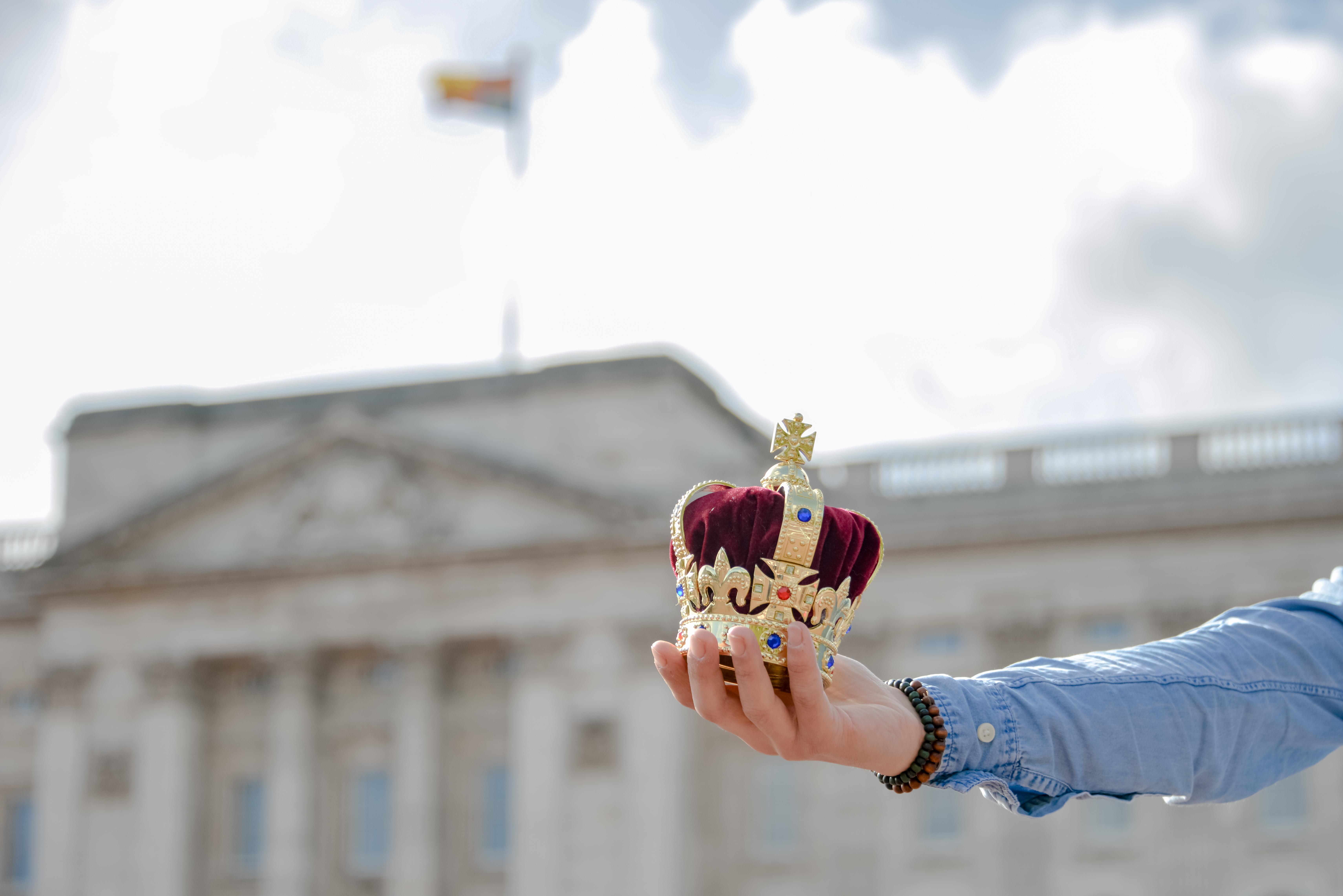 mão segurando coroa pequena na frente do palácio de buckingham com a rainha em londres