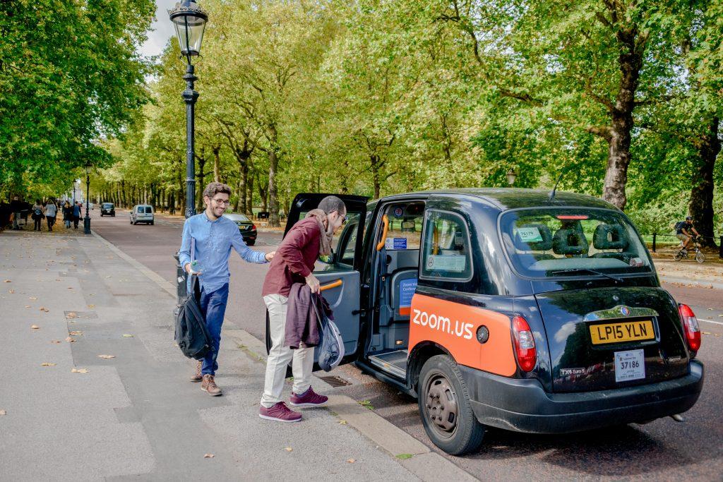 Homens entrando em um taxi preto em Londres. Black cab. The mall com árvores.
