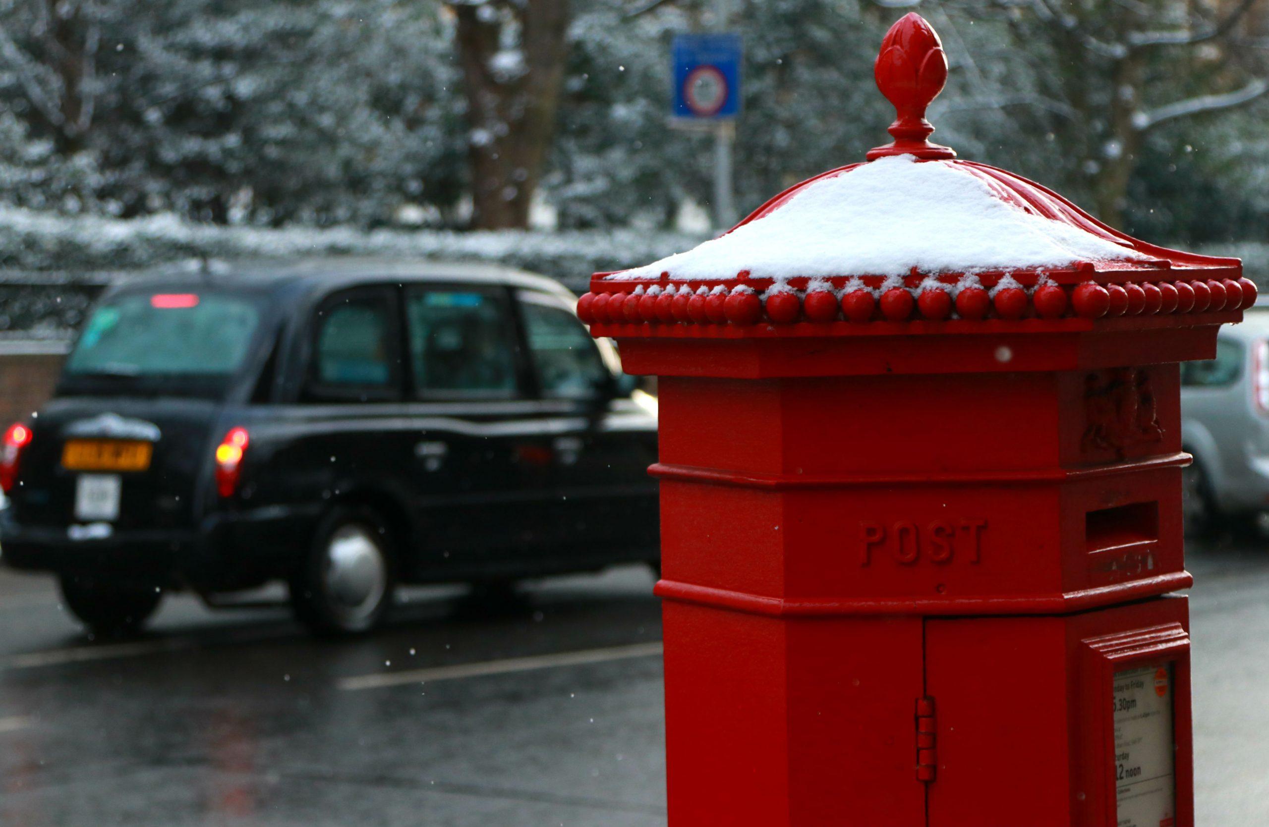 taxi preto londrino com caixa de correio bvermelha em um dia de neve