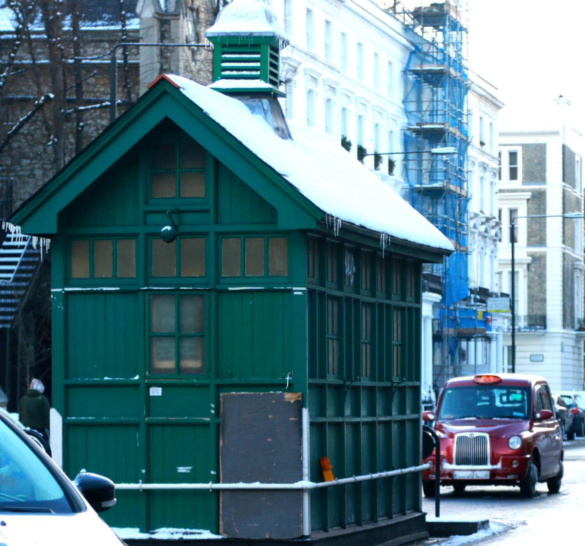 casinha verde de taxusta com tradicional taxi londrino vermelho ao fundo. tudo com neve.