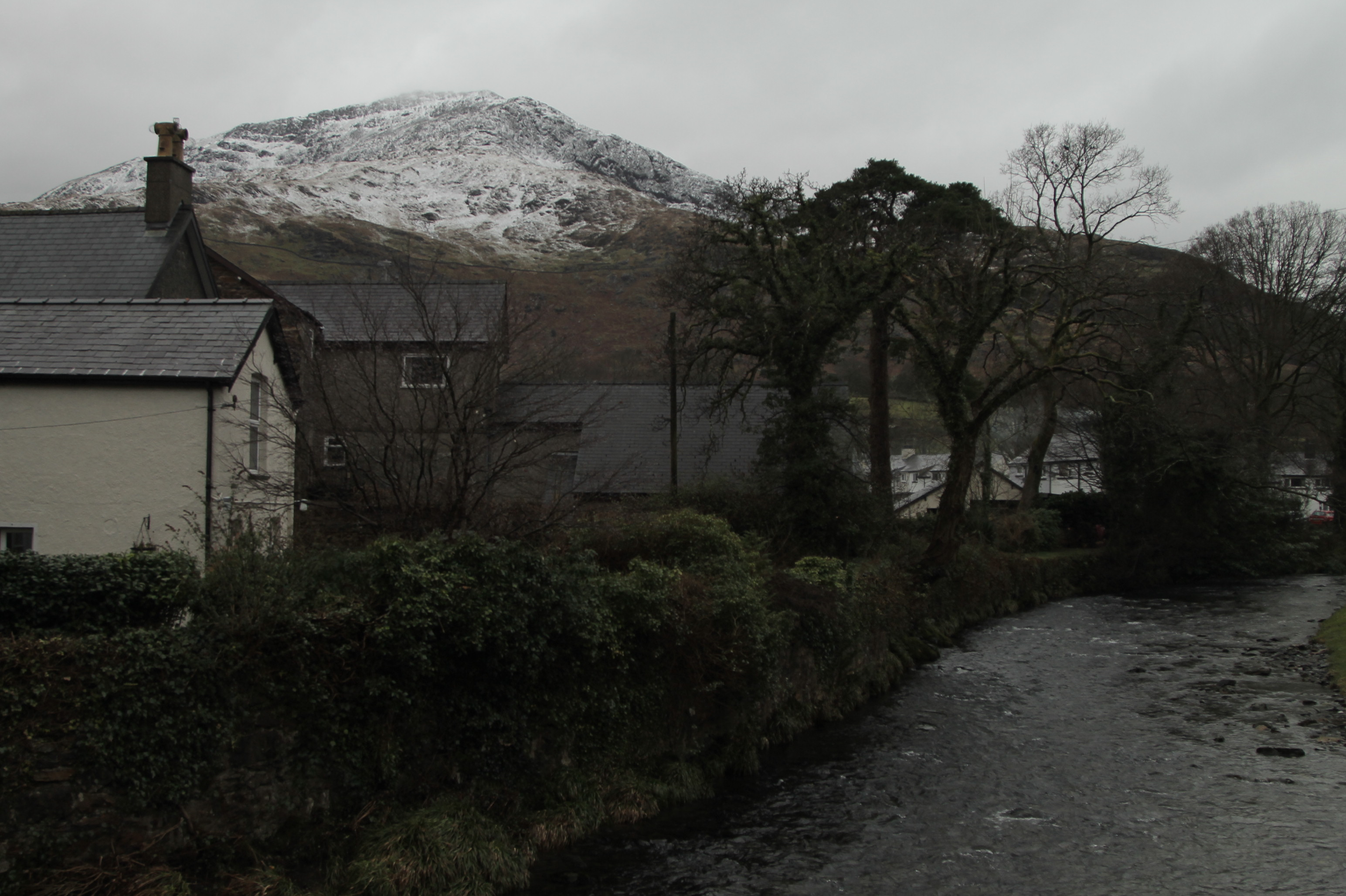 rio conwy em snowdonia, vila de beddgelert com arbores, casas de pedra e montanha com neve no fundo. paisagem linda.
