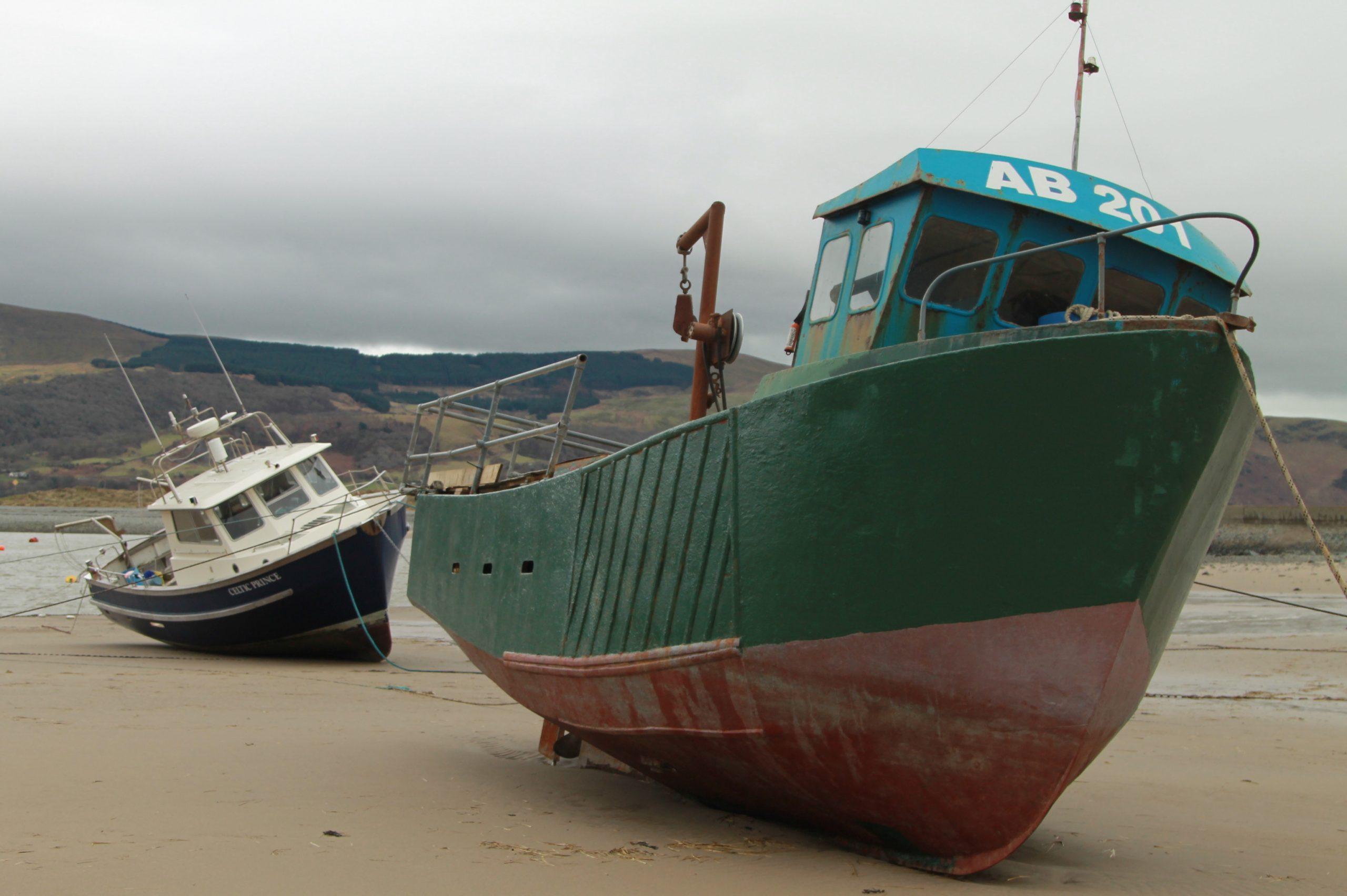 barco verde abandonado na margem da praia de barmouth no pais de gales