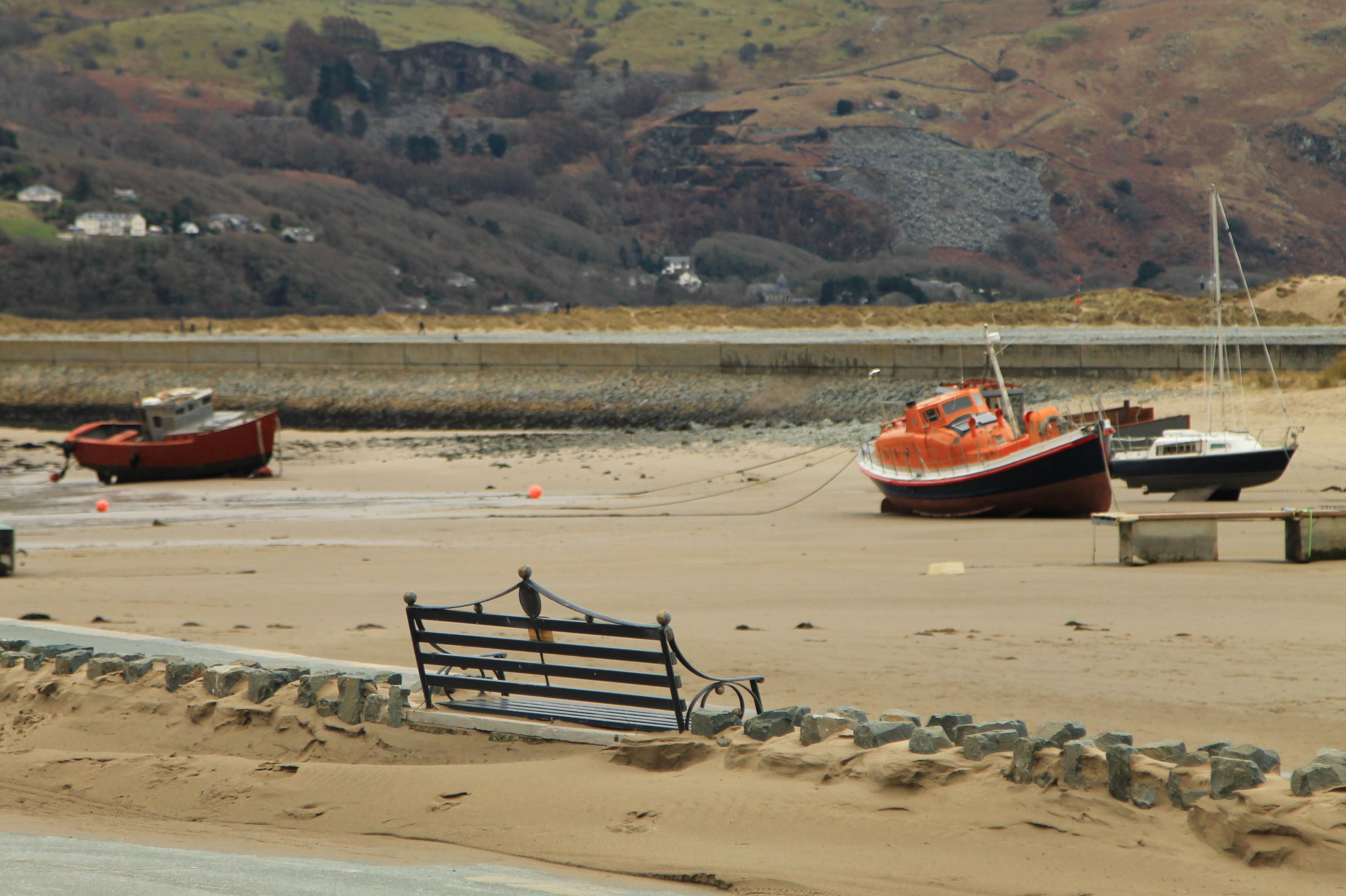 barco laranja abandonado em uma praia no inverno no pais de gales. barmouth.