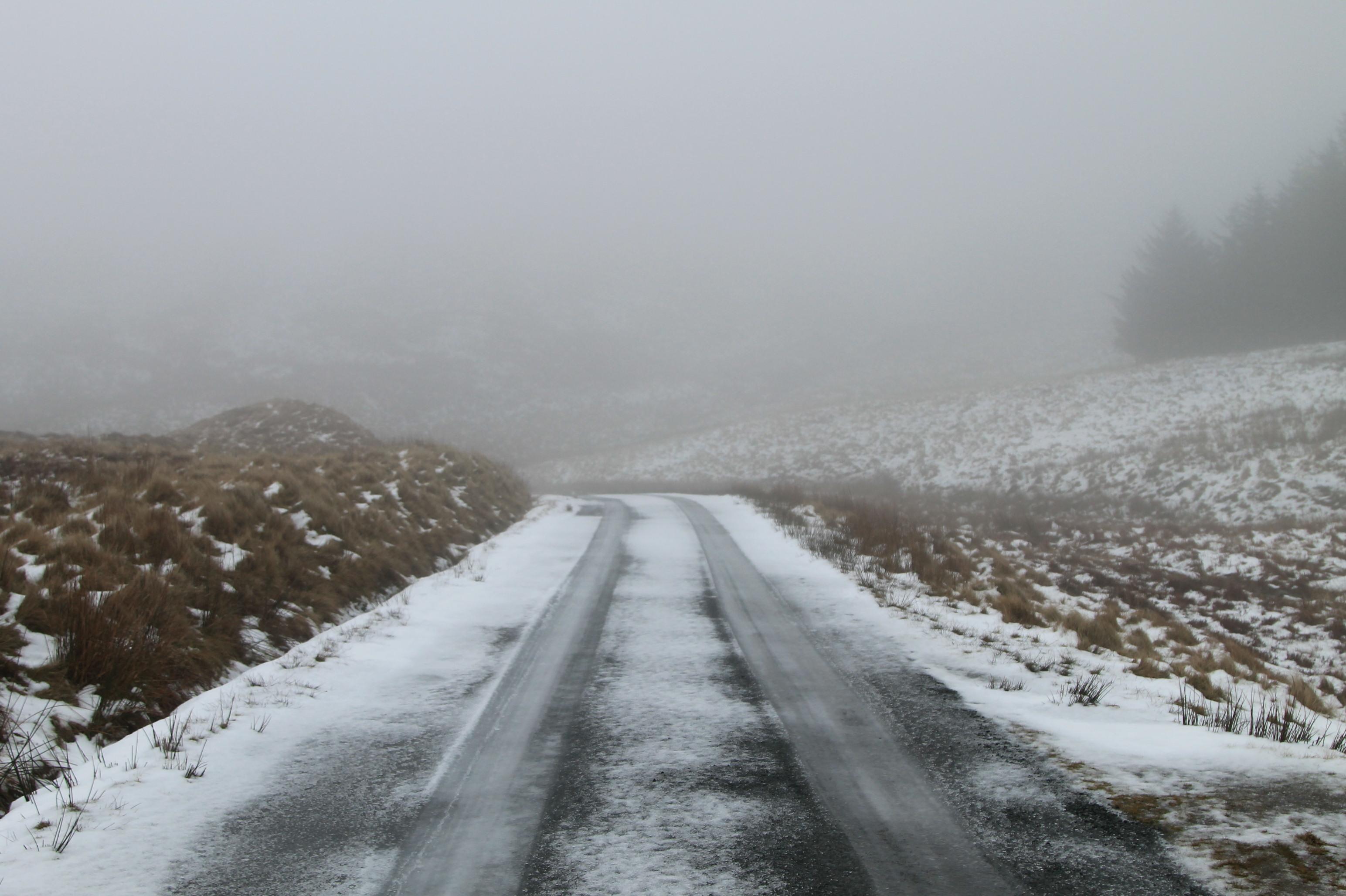 estrada com neve e marcas de roda no interior do pais de gales, snowdonia.