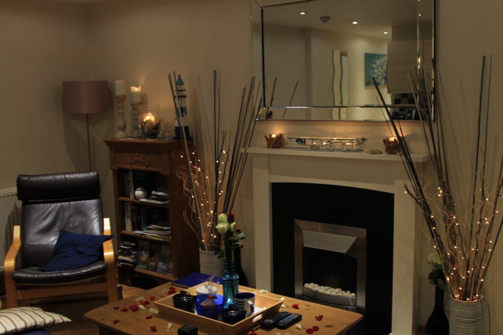 apartamento decorado com velas e lareira e umas prateleiras de madeira. airbnb no pais de gales