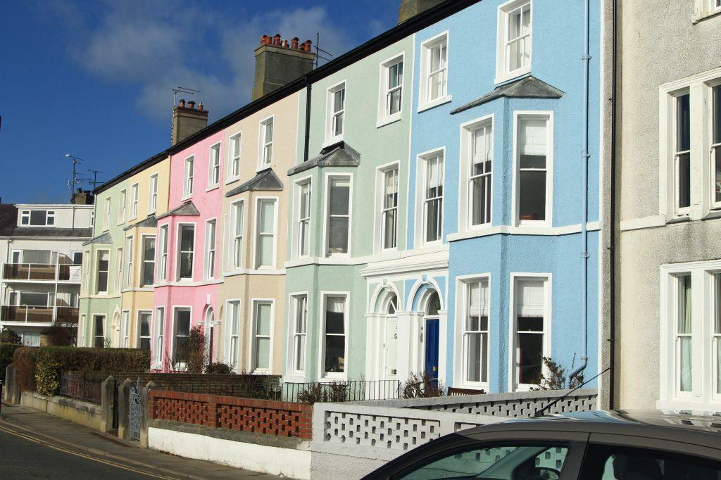 casas coloridas em anglesey, no interior do pais de gales. casas rosa, amarela, verde e azul.