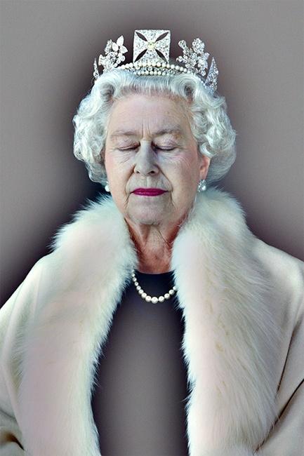 rainha elizabeth ii com coroa, casaco de pelo e olhos fechados.