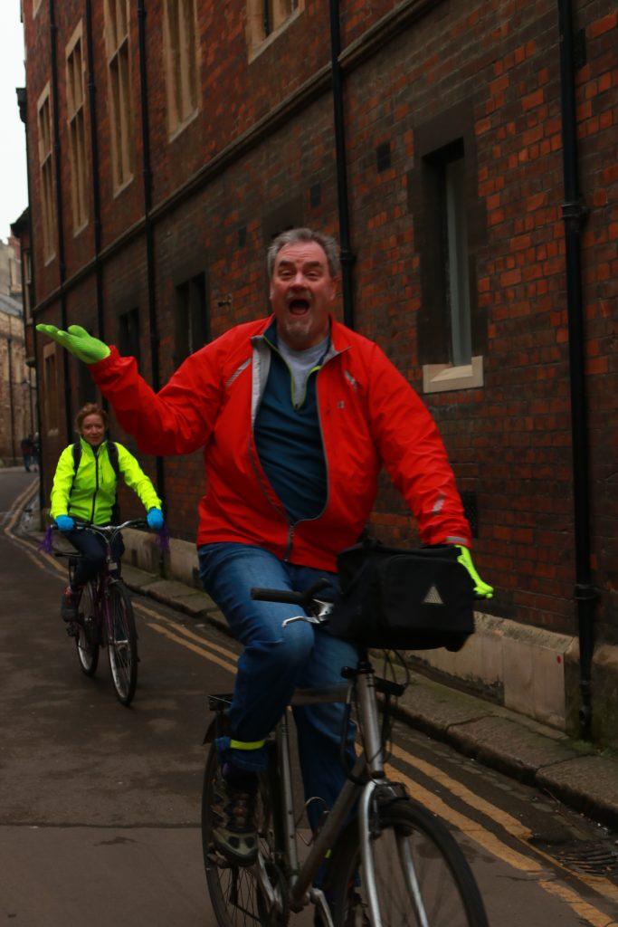 homem na bibibleta com jaqueta vermelha fazendo pose pra foto feliz em cambridge