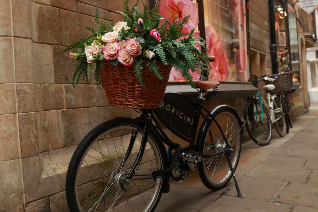 bicicleta da loja originis com flores na cestinha escorada na parede