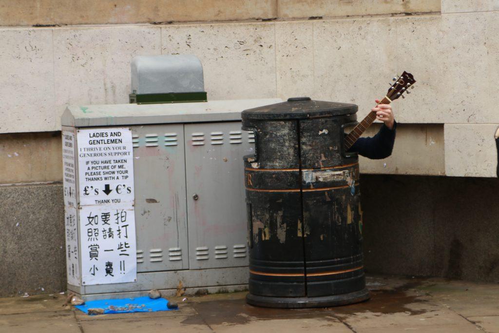artista de rua tocando dentro de lata de lixo em cambridge com uma placa em vários idiomas pedindo uma gorejta