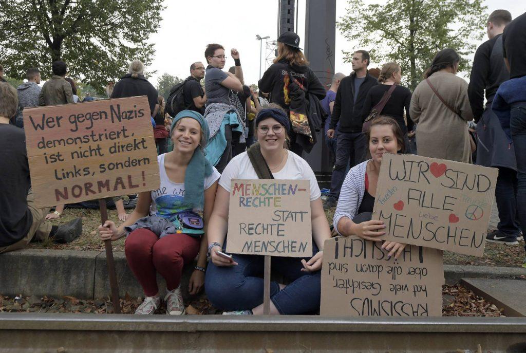 Pessoas com cartazes em alemão protestando contra os nazistas