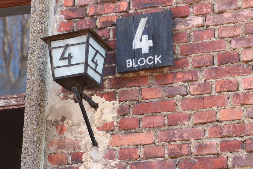 Bloco 4 de Auschwitz, placa de madeira com luminária ao lado