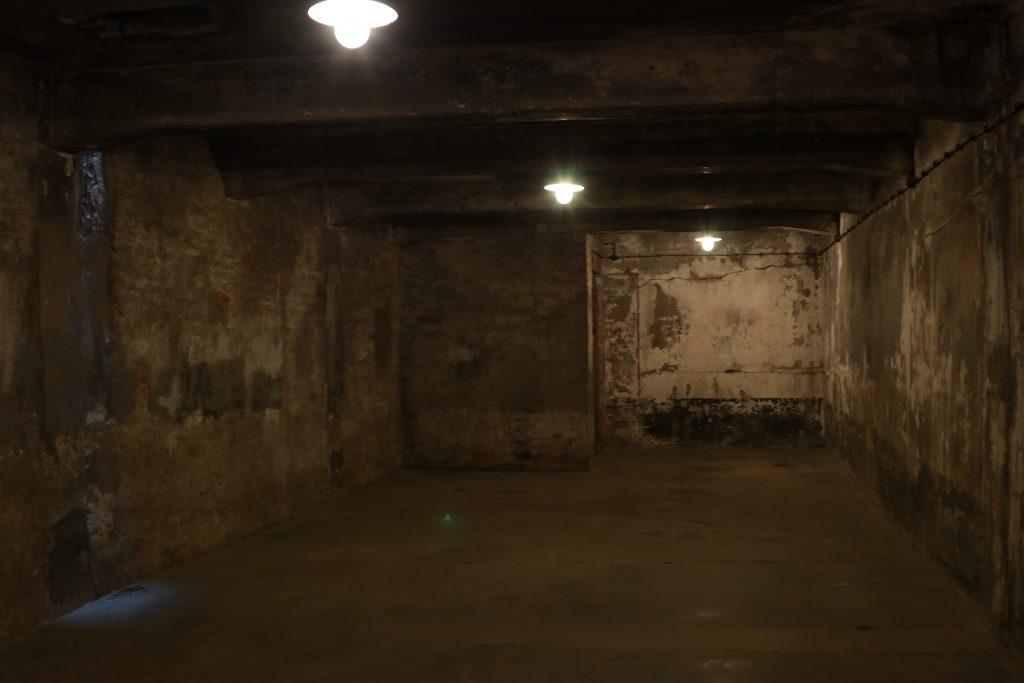 Câmara de gás de Auschwitz I (Crematorium I). Câmara ed tijolo com três luzes baixas e marcas nas paredes