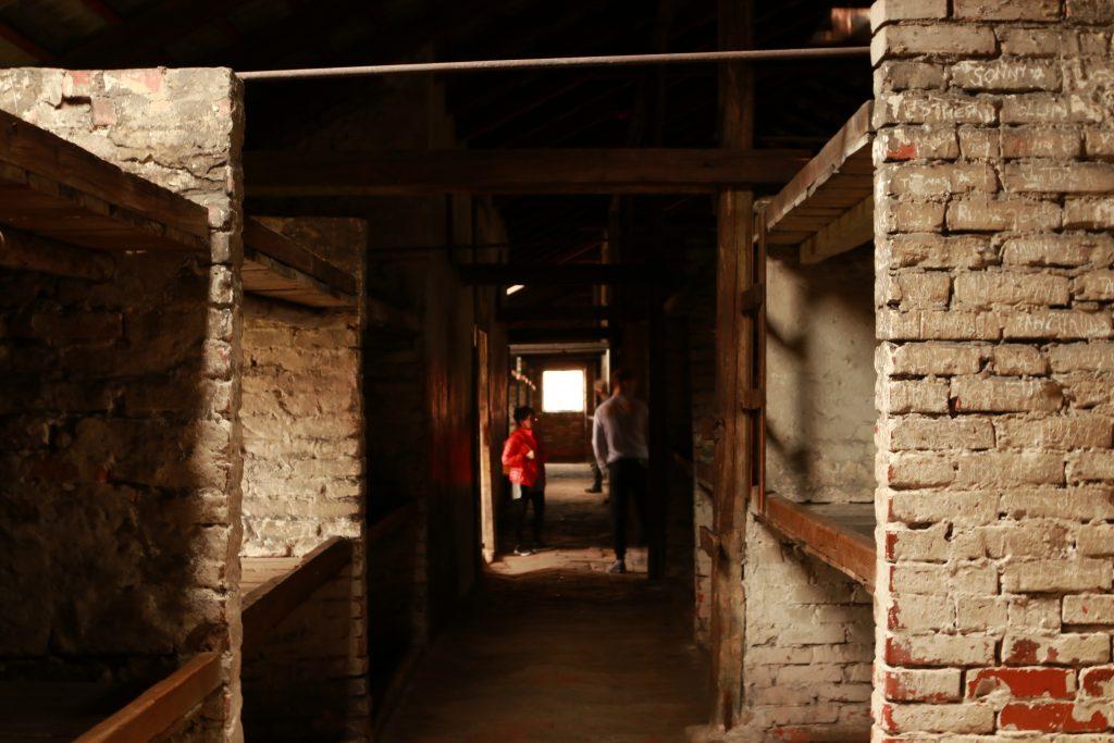 Alojamento de crianças em Auschwitz II-Birkenau, com fileiras de camas empilhadas de ambos os lados. Tudo feito de tijolo e frio