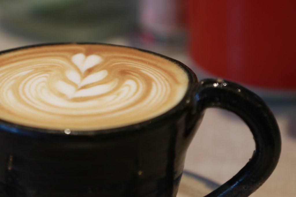 xicara preta de café flat white com decoração de tres corações