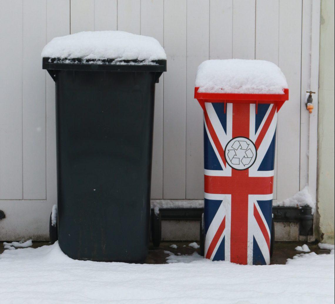 lixeiras com neve em cima, uma lixeira preta e a outra lixeira com a bandeira britanica