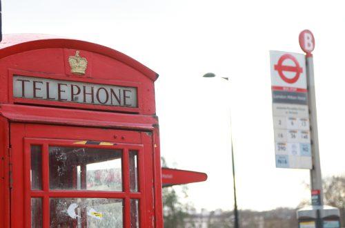 cabine telefônica vermelha famosa de Londres, com uma parada de ônibus do lado