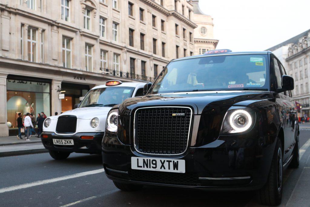 taxi de londres black cab levc eletrico hibrido sustentavel ao lado de um taxi tx4 branco motorista carlos na regent street