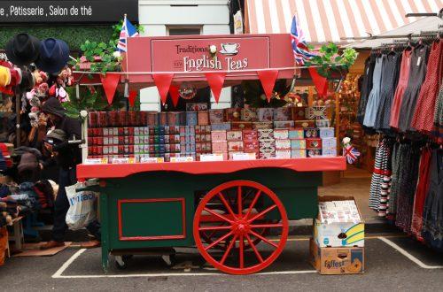 """carrinho vermelho de cha em notting hill com a escrita """"english tea"""" e varias caixas de chá"""