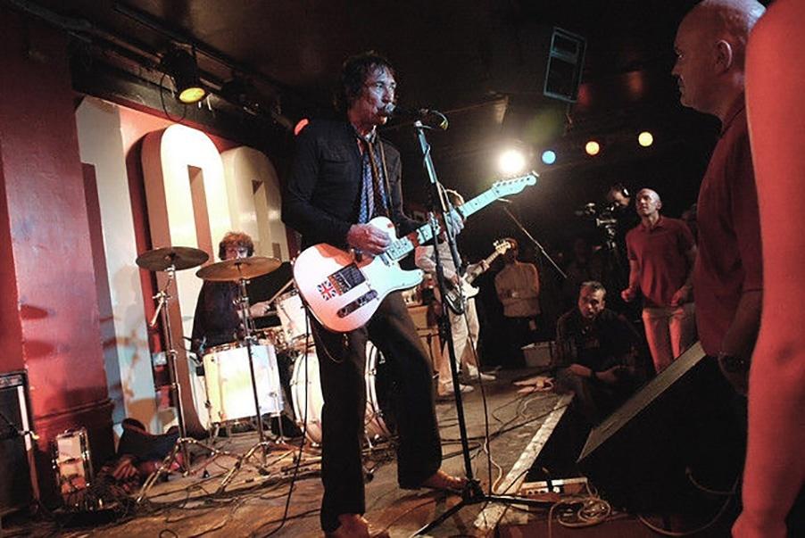 100 club com músico tocando guitarra no palco