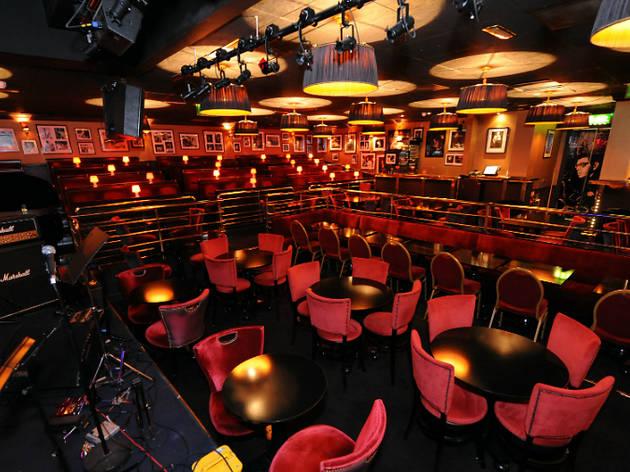 Ronnie Scott's clube de jazz com iluminação baixa e cadeiras vermelhas