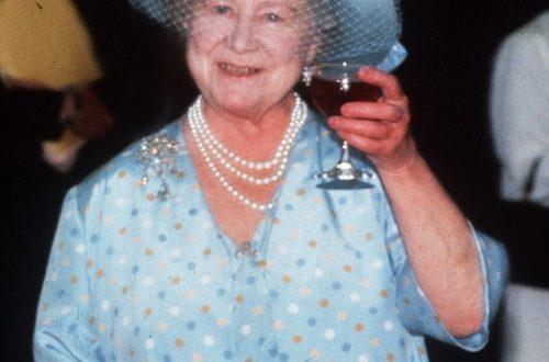 rainha mãe elizabeth bebendo uma taça de vinho com uma roupa azul e levantando a taça como quem está brindando.