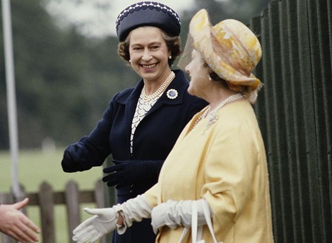 rainha mãe usando uma roupa amarela e chapéu amarelo cumprimentando charles, irmão da princesa diana, 9º earl spencer, ao lado da rainha elizabeth II usando uma roupa azul e por volta de 60 anos