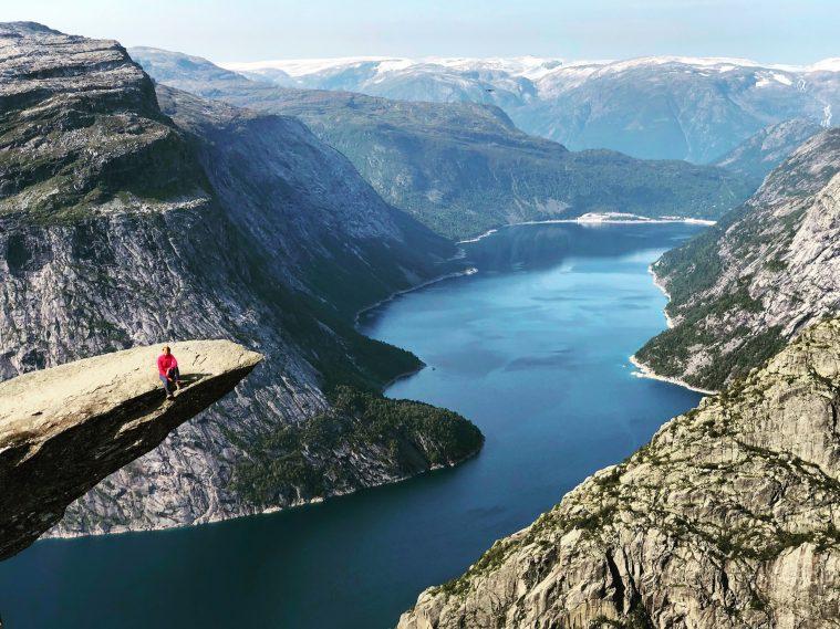 mulher sentada na ponta da pedra bem alta da trilha trolltunga com vista pro fiorde, no norte da noruega
