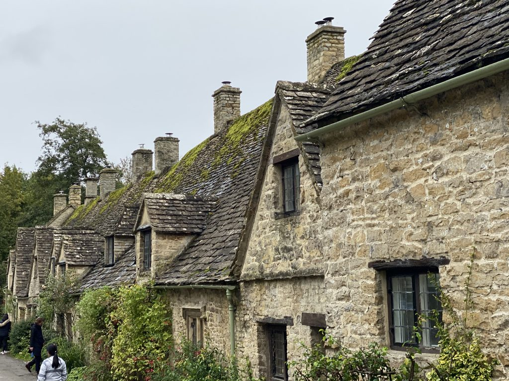 fileira de casas de pedra e tijolo a vista com céu nublado na vila de Bibury em Cotswolds no interior da inglaterra