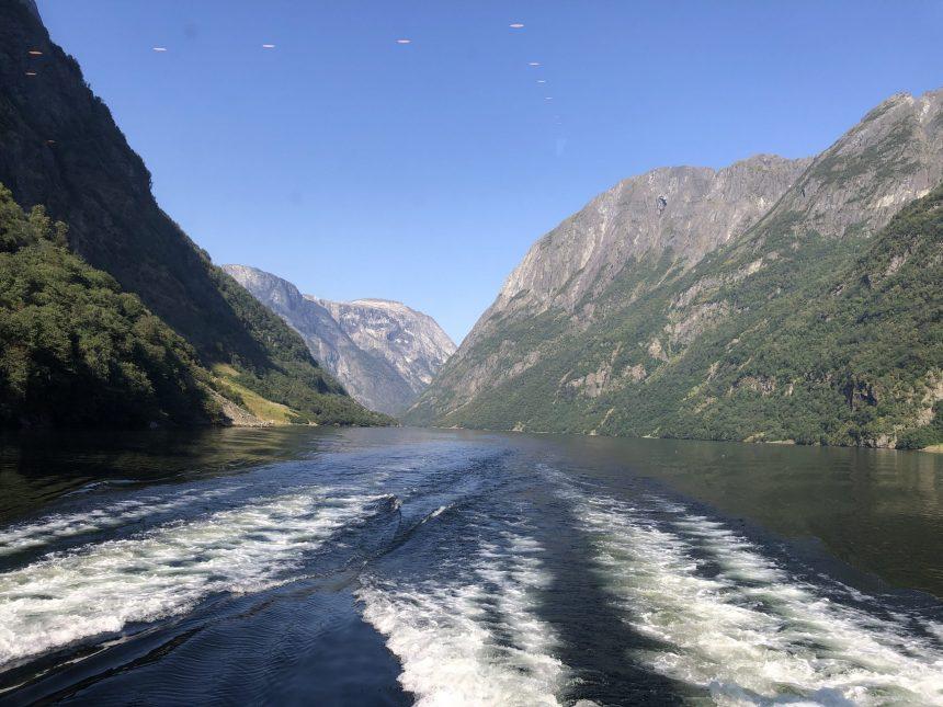 passeio de barco pelos fiordes da noruega com montanhas altas de ambos os lados