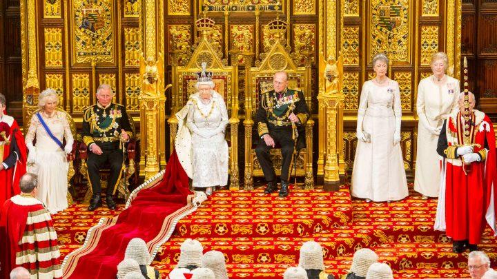 rainha elizabeth ii com coroa na cabeça e capa sentada no trono ao lado do principe philip e principe charles na camara dos lordes no parlamento britânico em londres