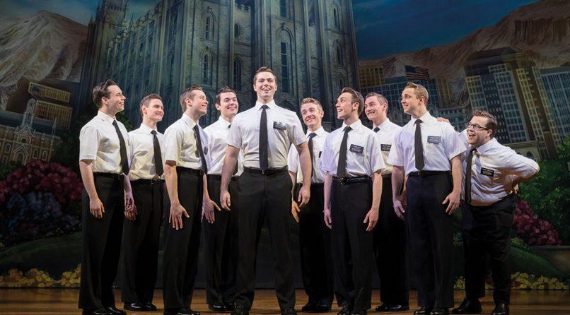 atores em ação na peça de teatro book of mormon em Londres, homens engravatados olhando para um deles